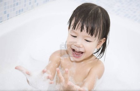 funny baby with hands in soapy foam laughing in bath