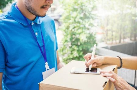 Woman appending sign signature after accepting a delivery of boxes from deliveryman, receive and delivery concept