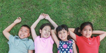 Photo pour Quatre enfants couchés sur l'herbe verte et regardant vers le haut dans le parc - image libre de droit
