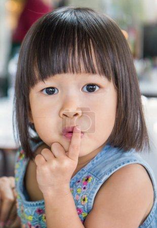 Portrait of little asian girl with finger near lips looking at camera