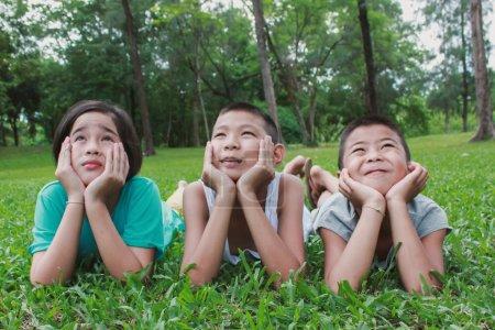 Photo pour Trois enfants couchés sur l'herbe verte, étayant les têtes avec les mains et passer du bon temps dans le parc - image libre de droit