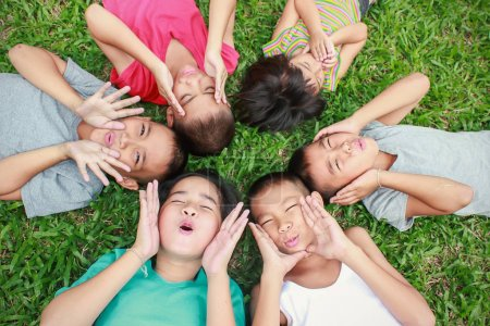 Photo for Six kids lying on green grass, looking up and having good time in park - Royalty Free Image