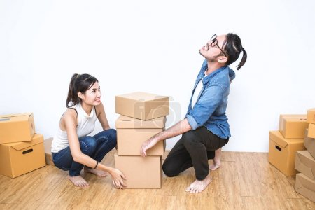 Asian woman and man in denim clothes working with boxes on floor