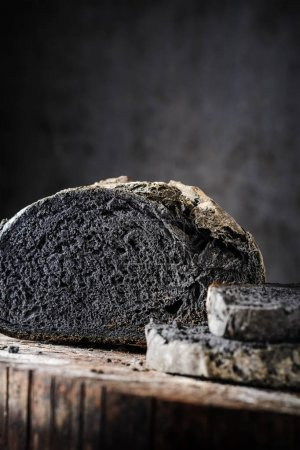 Sliced bread of black color on a wooden table