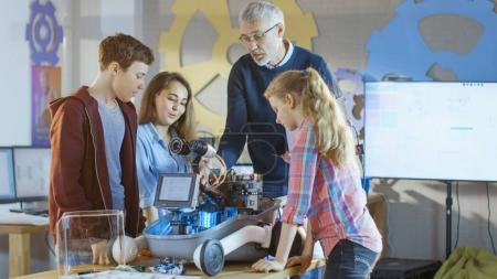 Teacher and His Pupils Work on a Programable Robot with LED Illu
