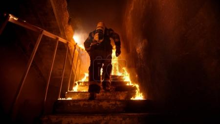 Strong and brave Firefighter Going Up The Stairs in Burning Buil