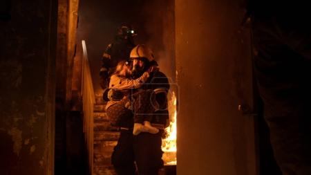 Brave Fireman Descends Stairs of a Burning Building with a Saved