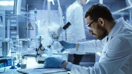 Photo pour Dans un laboratoire de recherche chimique, un scientifique mélange des composés du tabac dans des béchers . - image libre de droit