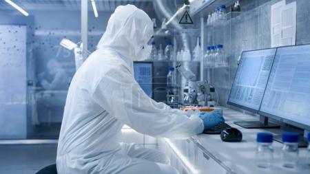 In a Secure High Level Laboratory Scientists in a Coverall Condu