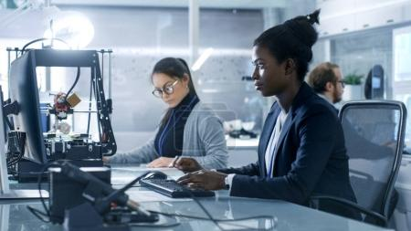Black Female Scientist Working on a Computer with Her Colleagues