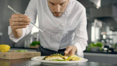 Famous Chef Decorates His Special Fish Dish with Some Greens. He