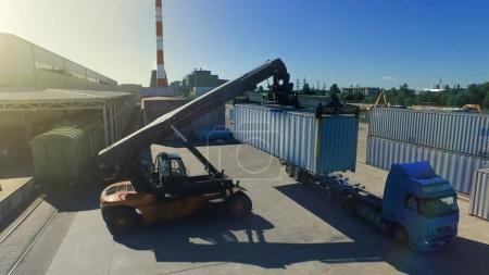 Container Handler is Loading Container onto Truck in Logistic Ce