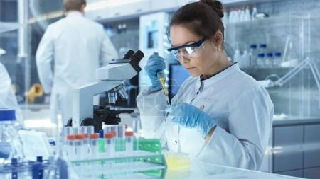 Female Research Scientist Uses Micropipette Filling Test Tubes i