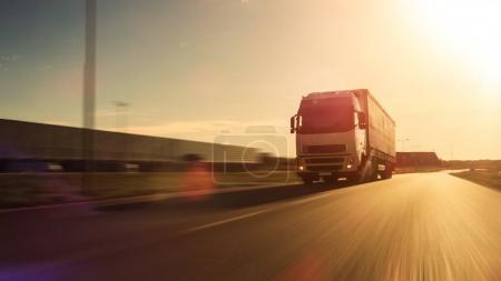 Photo pour Camion blanc Semi avec remorque attachée lecteurs sur la route de vide. Entrepôts industriels par les côtés de la route. Coucher du soleil. Flou de mouvement. - image libre de droit