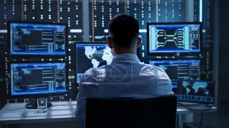 Photo for System Security Specialist Working at System Control Center. Room is Full of Screens Displaying Various Information. - Royalty Free Image