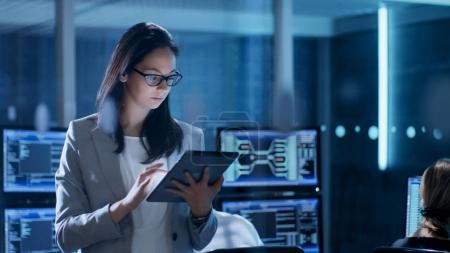 Young Female Government Employee Wearing Glasses Uses Tablet in