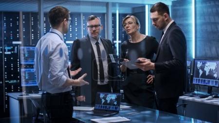 Photo pour Équipe de dirigeants d'entreprise ayant la réunion en salle de surveillance. Ils sont dans des installations de pointe. Les ordinateurs ont des écrans animés. - image libre de droit
