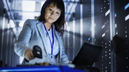 Asian Female IT Engineer Working on a Laptop on Tool Cart, She S