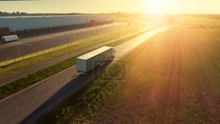 Photo for Aerial Shot of White Semi Truck with Cargo Trailer Attached Moving Through Industrial Warehouse, Rural Area. Sun Shines and the Sky Are Blue. - Royalty Free Image