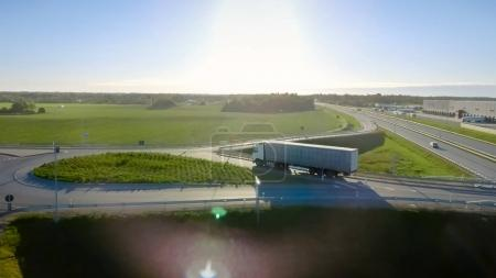 Aerial View of White Semi Truck with Cargo Trailer Passing Highw