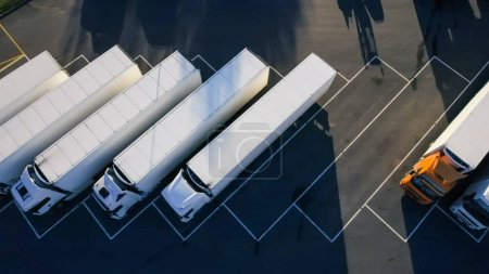 Aerial Top View of White Semi Truck with Cargo Trailer Parking with Other Vehicles on Special Parking Lot.