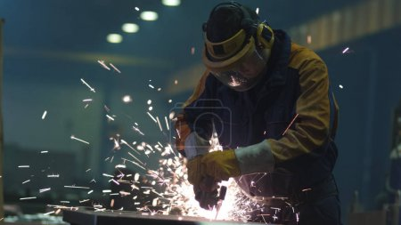Heavy industry worker at a factory is working with metal on a an