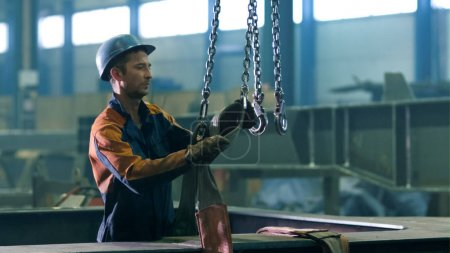Heavy industry worker at a factory is working with hooks from a