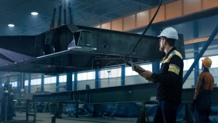 Photo pour Les travailleurs de l'industrie lourde déplacent un objet de construction métallique massif dans une usine . - image libre de droit