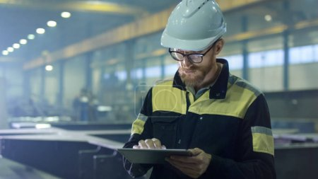Engineer in hardhat is using a tablet computer in a heavy indust