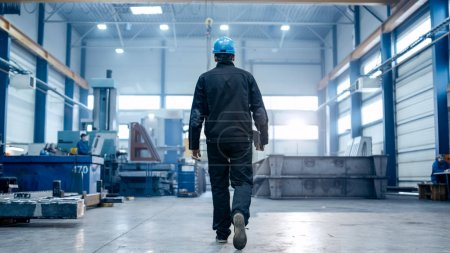 Factory worker in a hard hat is walking through industrial facil