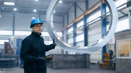 Factory worker in a hard hat is moving a metal detail with a rem