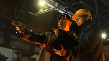 Engineer and Worker Have Conversation in Foundry. Engineer Using