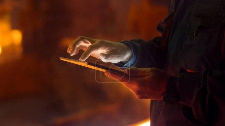 Engineer in Glasses using Tablet PC in Foundry. Industrial Envir