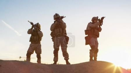 Squad of Three Fully Equipped and Armed Soldiers Standing on Hil