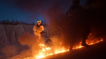 Group of Armed Soldiers Running through Fire During Night Milita