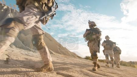 Squad of Fully Equipped and Armed Soldiers Moving in Single File
