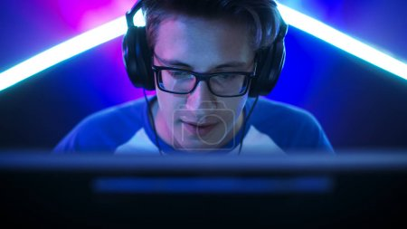 Photo for Professional Gamer Plays in MMORPG/ Strategy/ Shooter Video Game on His Computer. He's Participating in Online Cyber Games Tournament, Plays at Home, or in Internet Cafe. He Wears Glasses and Gaming Headphones, Talks into Microphone. - Royalty Free Image