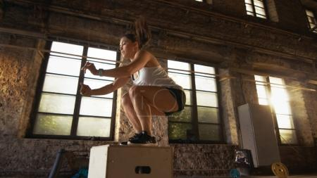 Photo for Fit Athletic Woman Does Box Jumps in the Deserted Factory Gym. Intense Exercise is Part of Her Daily Cross Fitness Training Program. - Royalty Free Image