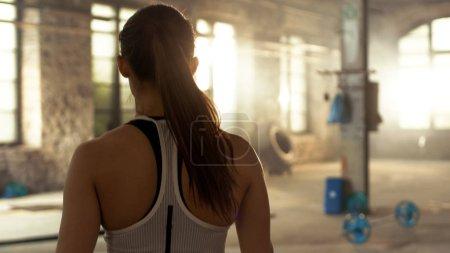 Photo pour Tiré de l'arrière du sportif belle femme entrant Gym. Elle est confiant, bâtiment industriel et Hardcore, diverses remise en forme de croix / équipement de musculation gisant sur le sol. - image libre de droit