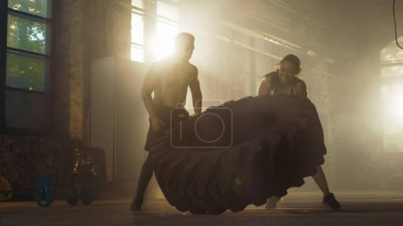 Photo for Fit Athletic Woman Lifts Tire Under Supervision of Her Partner/ Trainer, as Part of Her Cross Fitness/ Bodybuilding Gym Training. - Royalty Free Image