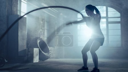 Strong Athletic Woman Exercises with Battle Ropes as Part of Her