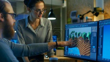 Photo pour Développeur de jeu masculin parle avec concepteur artistique de niveau féminin. Deux affichages montrent jeu totalement original. Ils travaillent dans un loft de bureau créatif . - image libre de droit