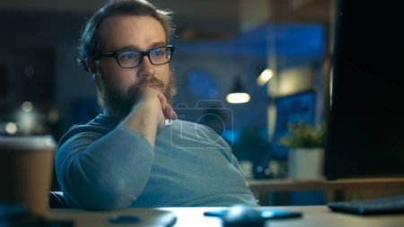 Focused Young Man Sits at His Desk and Thinks on a Problem Solut