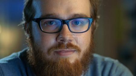 Photo pour Gros plan d'un jeune homme créatif barbu avec des lunettes regarde sournoisement dans la caméra . - image libre de droit