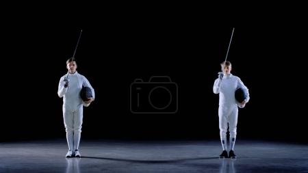 Two Young Professional Fencers Greet Audience, and Preparing for Fighting Match. Shot Isolated on Black Background.