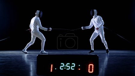 On the Championship Two Professional Fully Equipped Fencers Fight with Foils while Scoreboard Keeps the Scores of Hits. Shot on Isolated Black Background.