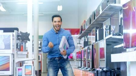 In the Electronics Store Young Man Holds Newly Purchased Compute
