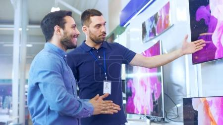 In the Electronics Store Professional Consultant Shows Latest 4K