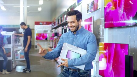 Young Man in Electronics Store Purchased Latest Model of the Tab