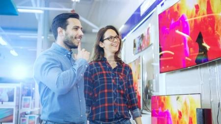 Young Couple Shopping for a New 4K TV Set in the Electronics Sto